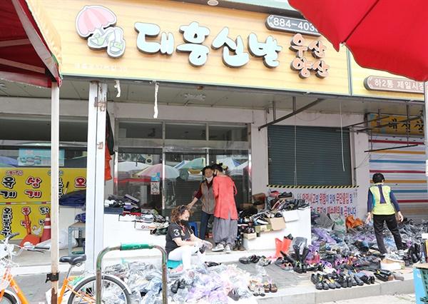 시장 폐쇄 후 남은 신발을 팔고 있는 할머니와 손님 시장 폐쇄 후 남은 신발을 팔고 있는 할머니와 손님