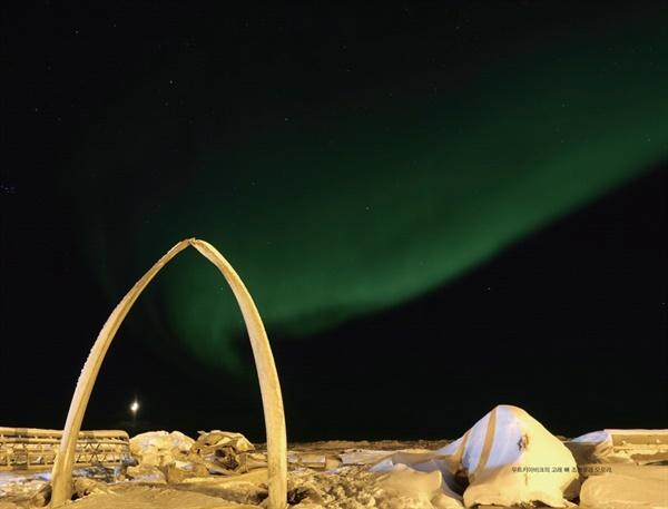 알래스카 우트키아비크의 고래 뼈 조형물과 오로라