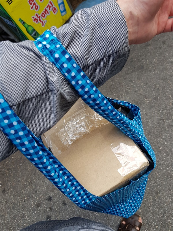 출근길에 택배를 친환경 봉투에 넣어 가지고 나오는 모습