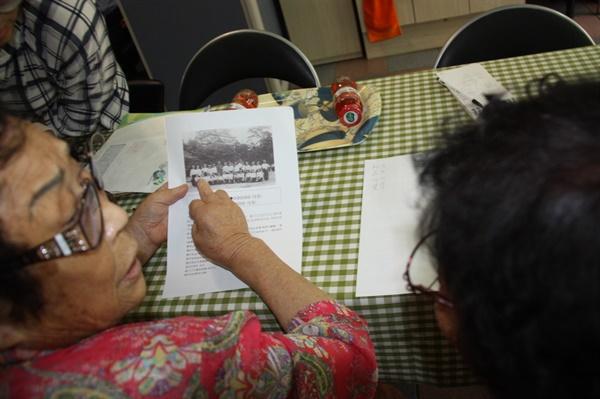나주에서 근로정신대로 동원됐다가 광복 72년만에 처음 만난 양금덕할머니가 사진 속에서 정신영 할머니를 가리키고 있는 모습. 아래 줄 왼쪽에서 두번째가 정신영 할머니. 2017년 8월