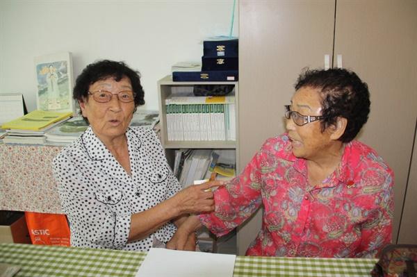 일본에서 돌아온 후 72년 만에 만난 정신영 할머니와 양금덕할머니가 반가워 서로를 가리키며 옛 추억을 꺼내고 있는 모습