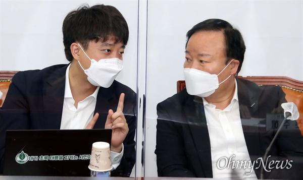 국민의힘 이준석 대표(왼쪽)가 22일 국회에서 열린 최고위원회의에서 김재원 최고위원과 대화하고 있다.