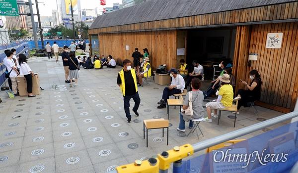 서울시 관계자들(왼쪽)이 23일 오후 서울 종로구 광화문광장에 있는 '세월호 기억공간'에서 보관된 물품을  옮기려하자, 유가족과 시민들이 이를 저지하기 위해 모여 있다.