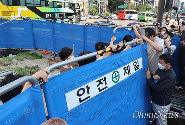 서울시 관계자들이 23일 오후 서울 종로구 광화문광장에 있는 '세월호 기억공간'에서 보관된 물품을  옮기려하자, 시민들이 이를 저지하기 위해 진입을 시도하고 있다.