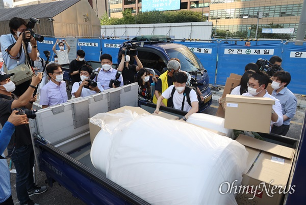 서울시 관계자들이 23일 오후 서울 종로구 광화문광장에 있는 '세월호 기억공간'에서 보관된 물품을  옮기는 계획이 유가족과 시민들에 의해 저지되자 가지고 온 박스를 챙겨 돌아가고 있다.
