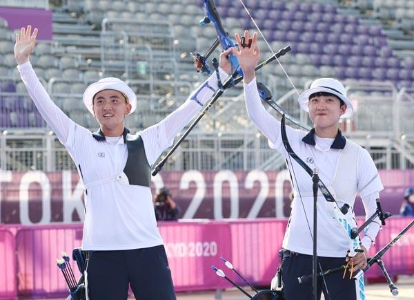 양궁 국가대표 김제덕(왼쪽)과 안산이 24일 일본 도쿄 유메노시마 공원 양궁장에서 열린 도쿄올림픽 혼성 결승전에서 금메달을 획득한 후 손을 흔들어 인사하고 있다.