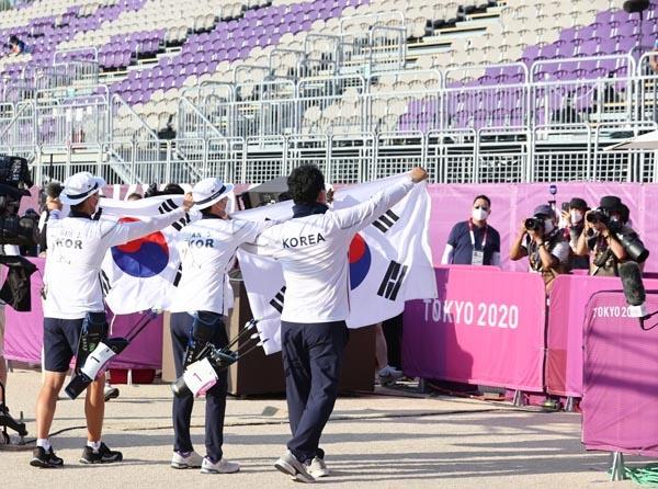 양궁 국가대표 김제덕과 안산이 24일 일본 도쿄 유메노시마 공원 양궁장에서 열린 도쿄올림픽 혼성 결승전에서 금메달을 획득한 후 태극기를 들어 보이고 있다.