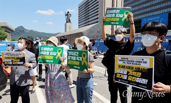 서울시가 광화문광장 재구조화 공사를 위해 광장에 있는 '세월호 기억공간' 철거를 예고한 26일 오전 서울 종로구 '세월호 기억공간' 앞에서 시민들이 기억관 철거 중단을 촉구하는 피켓을 들어보이고 있다.