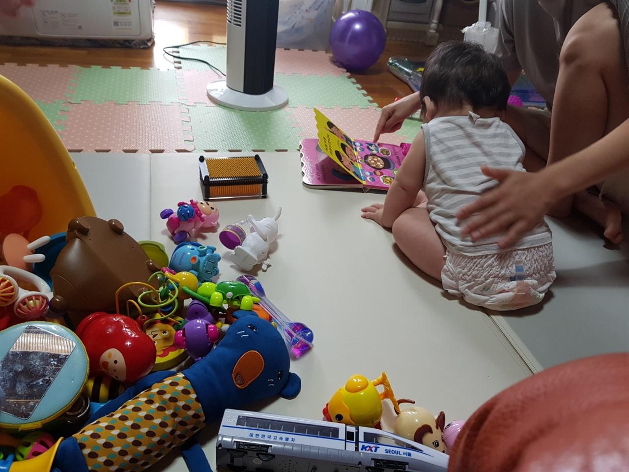 아기가 사운드 북을 읽고 있는 모습. 옆으로 아기의 장난감들이 보인다.