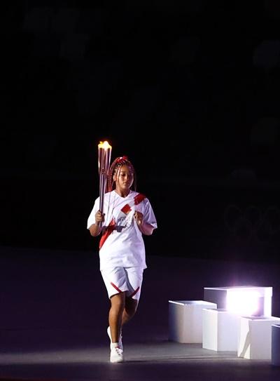 23일 일본 도쿄 신주쿠 국립경기장에서 열린 2020 도쿄올림픽 개막식에서 성화 최종주자 오사카 나오미가 어린이 선수들로부터 성화를 전달받고 성화대로 달리고 있다.