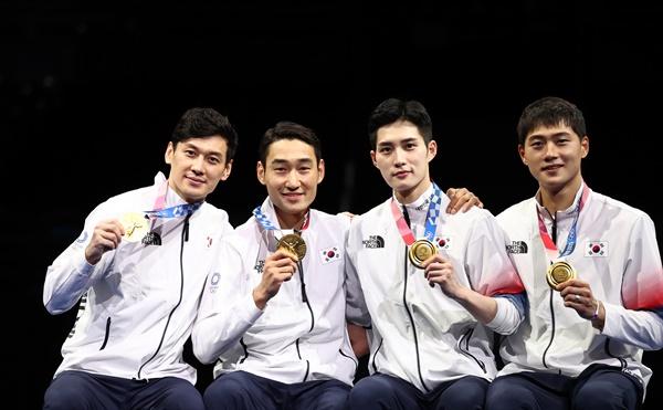 구본길, 김정환, 김준호, 오상욱이 28일 일본 지바의 마쿠하리 메세에서 열린 도쿄올림픽 남자 펜싱 사브르 단체전 시상식에서 금메달을 보여주며 있다.