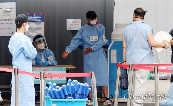 신종 코로나바이러스 감염증(코로나19) 4차 대유행으로 확진자가 급증하는 가운데 29일 서울 중구 서울역 광장에 마련된 코로나19 선별진료소에서 육군 현장지원팀이 시민들의 검사를 안내하고 있다.