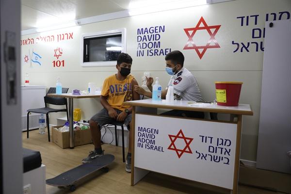 10대 청소년 대상 대규모 백신접종 나선 이스라엘  이스라엘이 신종 코로나바이러스 감염증(코로나19) 재확산으로 비상인 가운데 5일(현지시간) 텔아비브의 백신 접종소에서 한 소년이 코로나19 백신을 맞고 있다. 이스라엘은 학교를 중심으로 집단감염 사례가 잇따르자 12~18세 청소년을 대상으로 대대적인 백신접종 캠페인을 벌이고 있다