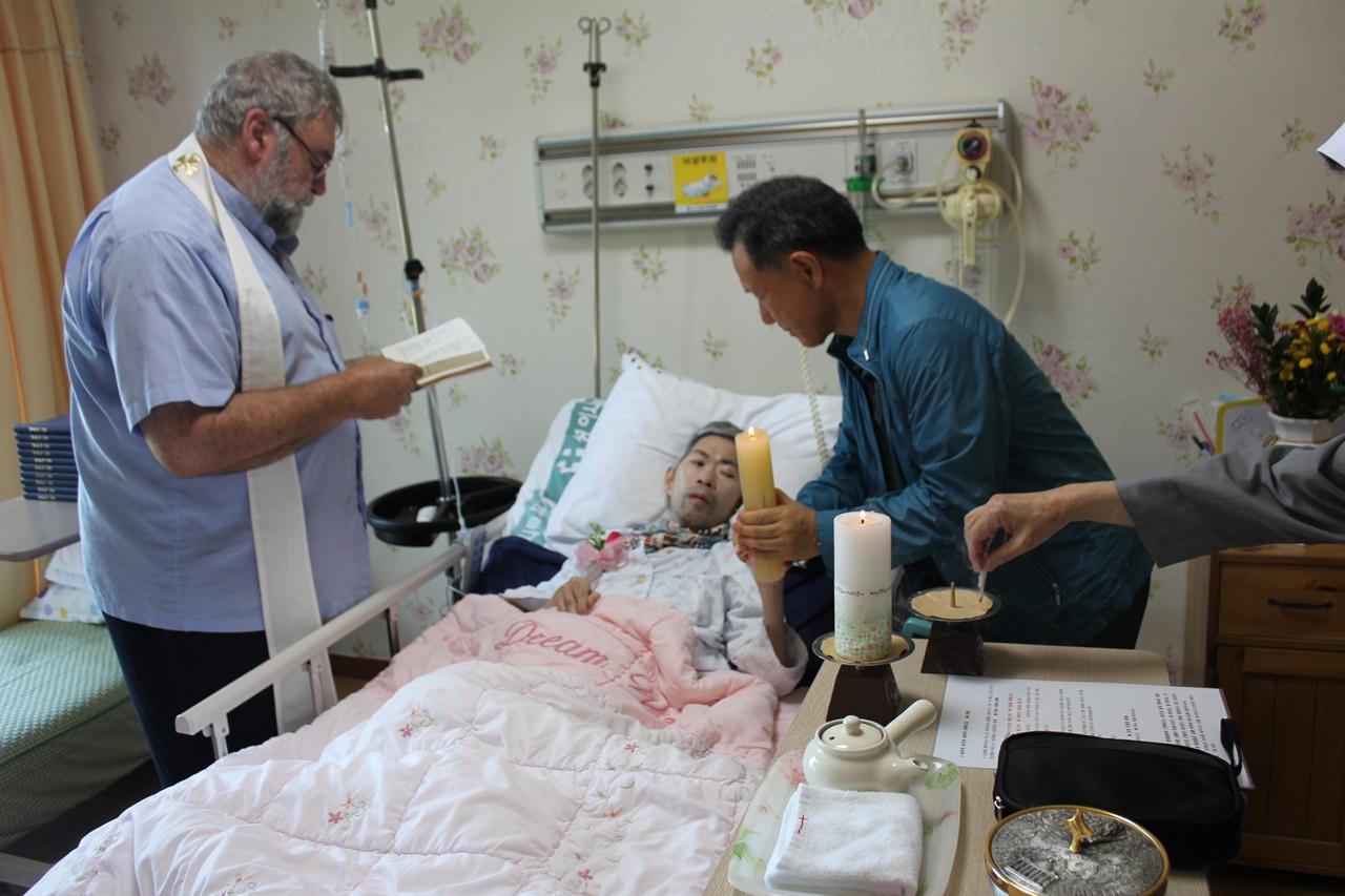 몸을 움직이지 못하고 말을 할 수도 없는 상태에서 병실에서 이뤄진 세례식.