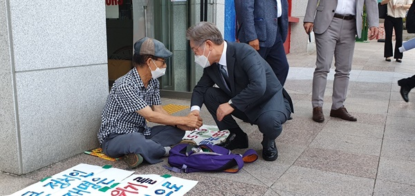 이재명 경기지사가 31일 오후 더불어민주당 경남도당 앞에서 박종권 경남기후위기비상행동 공동대표를 만나 손을 잡고 이야기를 나누고 있다