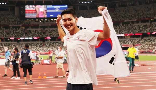 1일 도쿄올림픽 남자 높이뛰기에서 2m 35 한국신기록을 세우며 4위를 차지한 우상혁이 도쿄 올림픽스타디움에서 경기 종료 후 태극기를 펼치며 기뻐하고 있다. 2021.8.1