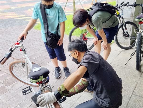 자전거 출장 수리 중 장인으로부터 설명을 듣고 있는 주민