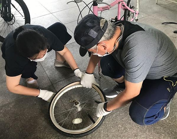 부부가 함께 나와 자전거 기초 수리 교육을 받는 모습