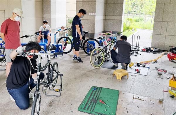 자전거 수리하는 장인들과 지켜보는 주민들