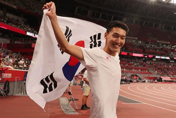1일 도쿄올림픽 남자 높이뛰기에서 2m35 한국신기록을 세우며 4위를 차지한 우상혁이 도쿄 올림픽스타디움에서 경기 종료 후 태극기를 펼치며 기뻐하고 있다.