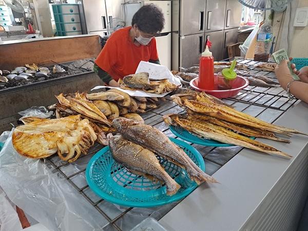 고흥 전통시장 숯불 생선구이 가게에서 한 고객이 숯불 생선구이를 구매하고 있다.