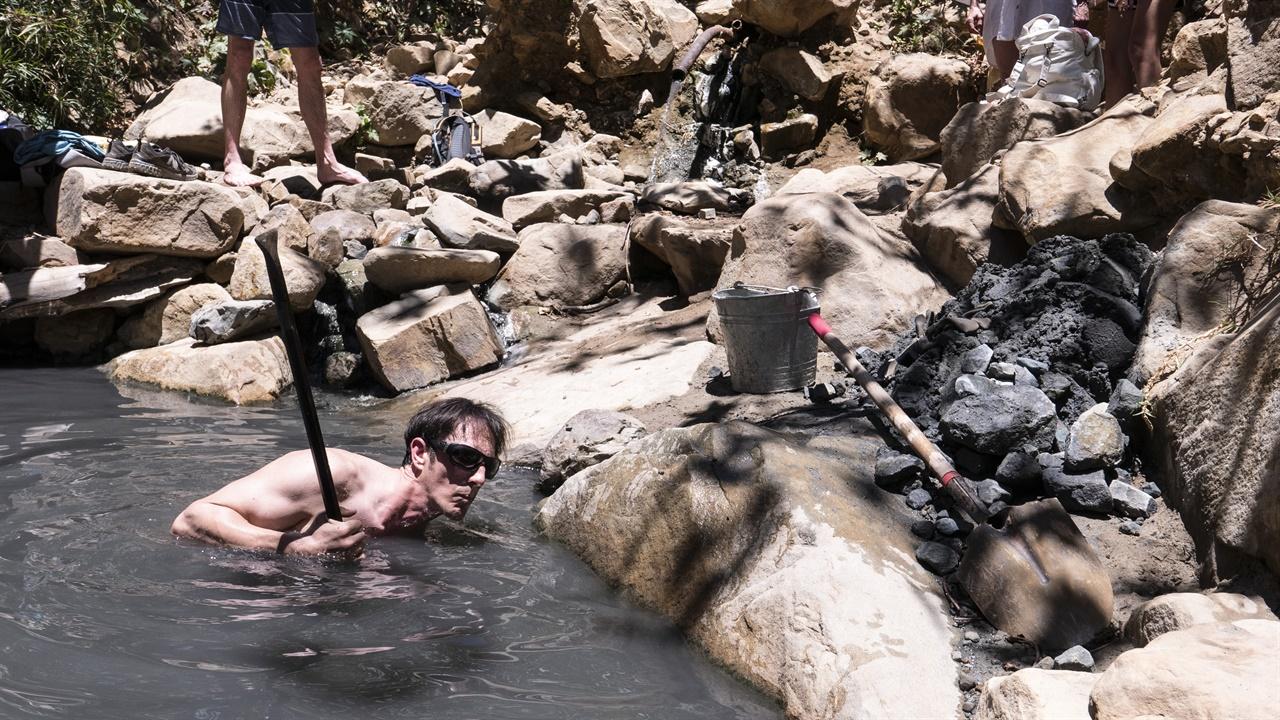 몬테시토 온천을 정비하고 있는 데렉. 파이프로 바닥을 뒤짚은 뒤 돌을 꺼내고 있다.