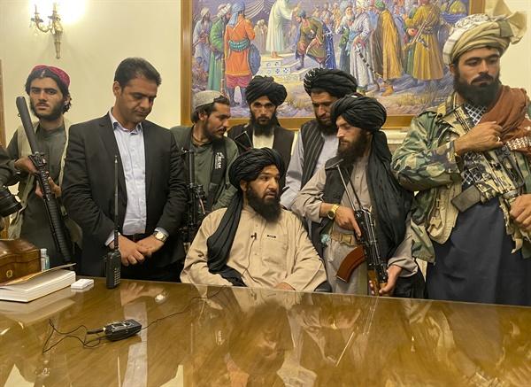 """아프가니스탄 무장단체 탈레반 조직원들이 15일(현지시간) 수도 카불에 위치한 대통령궁을 장악한 모습. 아프간을 장악한 탈레반은 이날 대통령궁도 수중에 넣은 뒤 """"전쟁은 끝났다""""며 사실상 승리를 선언했다. 아슈라프 가니 아프간 대통령은 앞서 이날 탈레반이 카불에 입성한 직후 국외로 도피했다."""