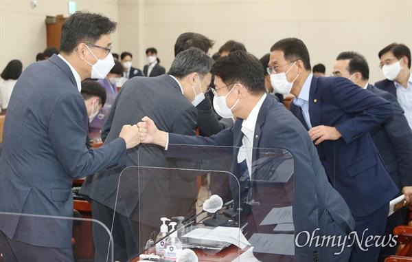더불어민주당과 국민의힘 의원들이 19일 서울 여의도 국회 기획재정위원회 전체회의에서 종부세 '과세기준 11억' 상향 개정안을 통과시킨 뒤 주먹을 맞대고 있다.