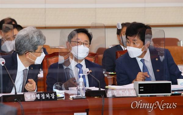 김상환 법원행정처장(왼쪽부터), 박범계 법무장관, 박종문 헌법재판소 사무처장이 24일 서울 여의도 국회 법제사법위원회에서 전체회의 개의를 기다리며 대화하고 있다.