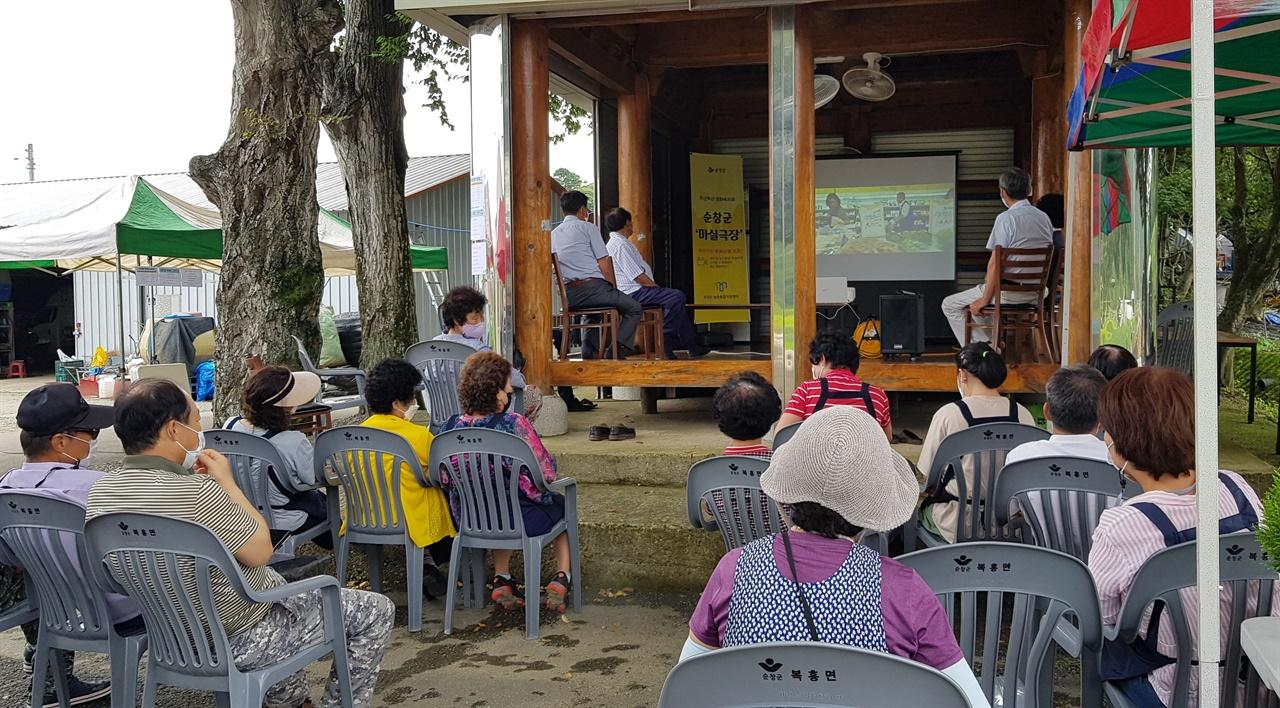 주민들이 마을 모정에 모여 영화 '장수상회'를 관람했다.