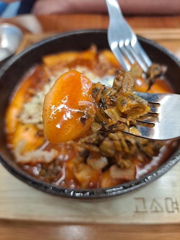 뜨거운 주물냄비에 담긴 맛있게 매운 떡볶이에는 어묵과 밀떡으로 만든 떡볶이가 가득하다.
