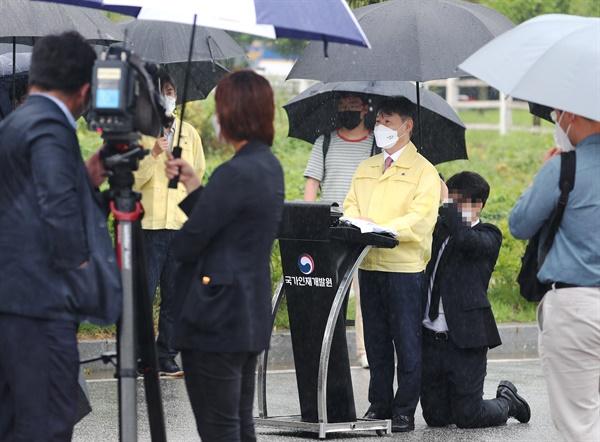 강성국 법무부 차관이 27일 오전 충북 진천 국가공무원인재개발원에서 아프가니스탄 특별입국자 초기 정착 지원과 관련해 브리핑하는 도중 관계자가 뒤쪽에서 무릎을 꿇고 우산을 받쳐주고 있다.