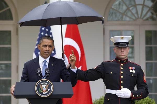 2013년 5월 16일 버락 오바마 미국 대통령이 백악관 로즈가든에서 열린 레제프 타이이프 에르도안 터키 총리와 공동 기자회견에서 발언하는 도중 비가 내리자 해병대원이 우산을 들고 있다.