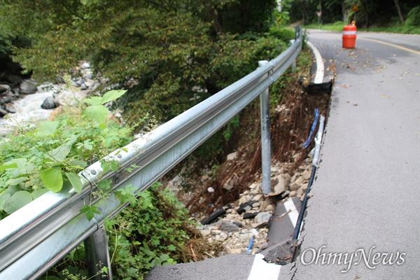 지난달 24일 태풍 '오마이스'의 영향으로 집중호우가 내리면서 경북 포항시 죽장면 두마리로 들어가는 도로의 일부가 무너져 가드레일 기둥이 드러나 있다.