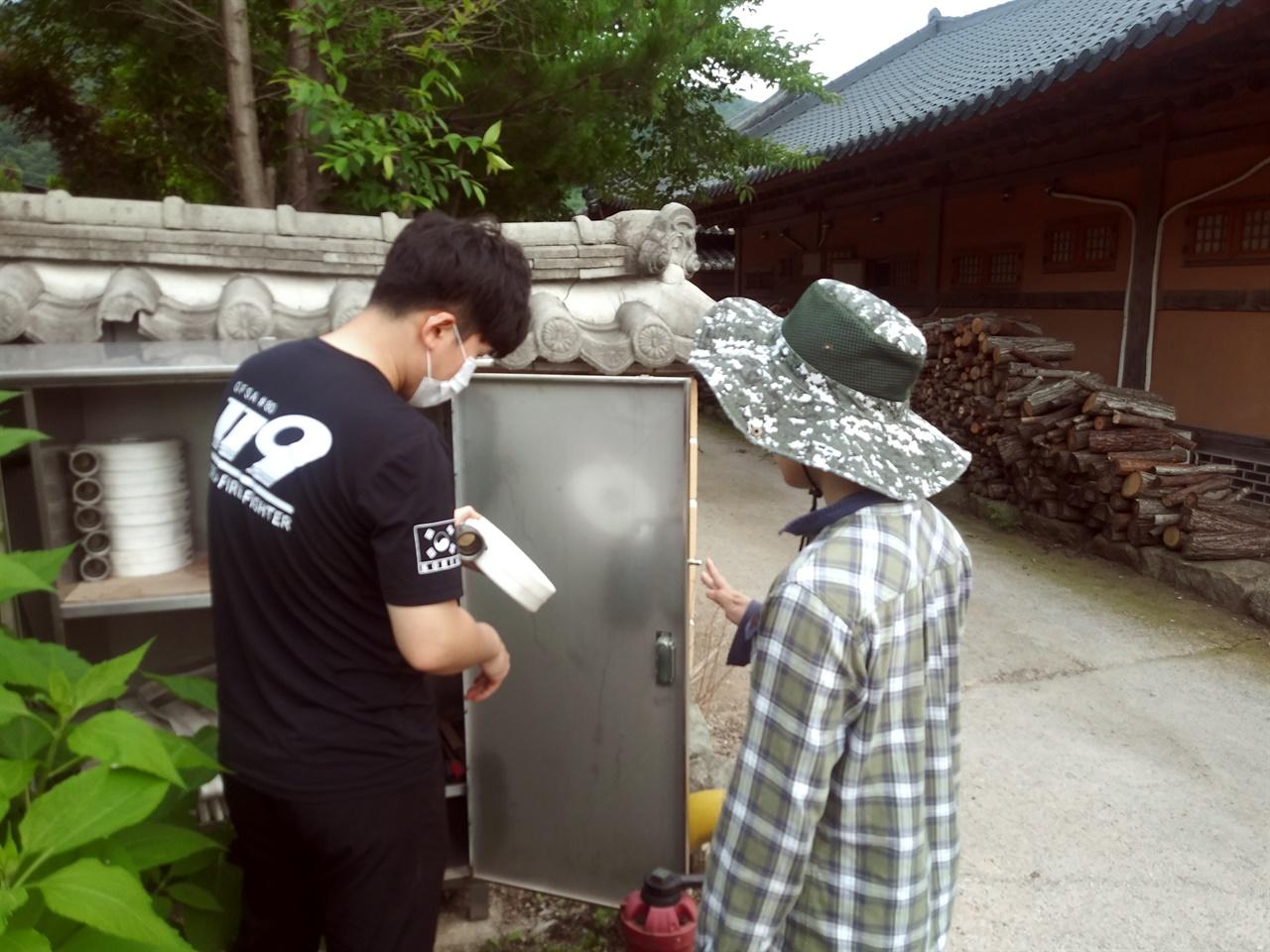 소방대원과 오두마을 이장이 함께 소방안전점검에 참여하고 있다.