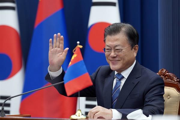 문재인 대통령이 10일 청와대에서 열린 우흐나 후렐수흐 몽골 대통령과의 화상 정상회담에서 손을 들어 인사하고 있다.