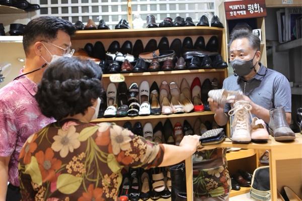 도현동 사장이 수선을 어떻게 진행할지에 대해 고객에게 설명하고 있다.