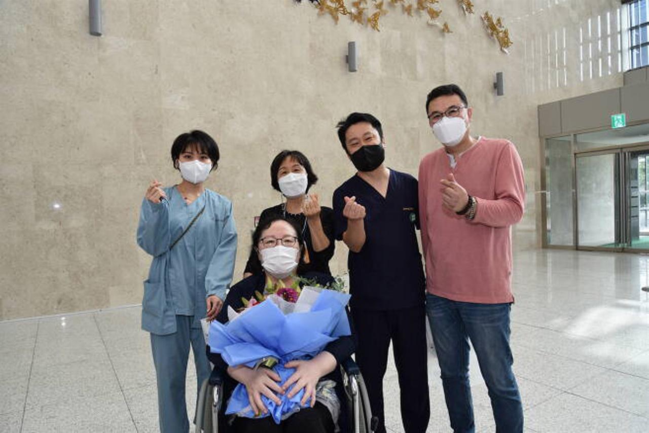 10일 코로나19로 혼수상태에 빠졌던 이 씨(앞줄)가 성남시의료원에서 에코모 치료 통해 건강하게 퇴원하며 의료진들과 기념사진을 찍고 있다.
