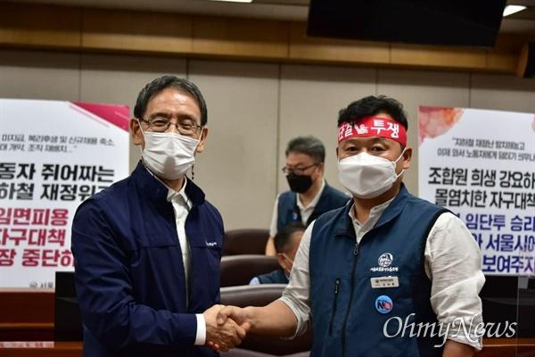 서울교통공사와 서울교통공사 노동조합이 13일 밤 서울 성동구 서울교통공사에서 노사합의서를 체결한 뒤 악수를 나누고 있다.