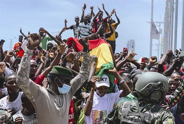 2021년 9월 5일 기니에서 쿠데타가 벌어졌다. 다음날인 6일 기니 코나크리에 있는 인민궁전 앞에서 기념행사가 진행되는 동안 기니 국민들이 국기를 흔들며 축하하고 있는 모습.