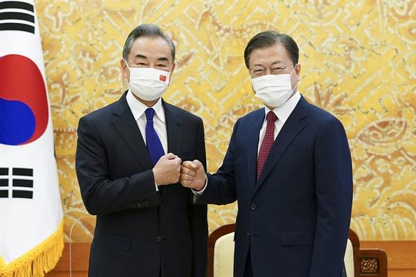 문재인 대통령이 15일 청와대에서 왕이 중국 외교부장을 접견했다. 문 대통령이 접견에 앞서 기념촬영을 한 뒤 왕 부장과 주먹인사를 나누고 있다.