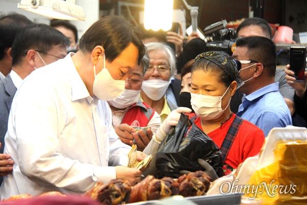 국민의힘 윤석열 대통령선거 경선후보가 18일 오후 창원 마산어시장을 찾아 한 가게에서 돼지족발을 구입하고 있다.