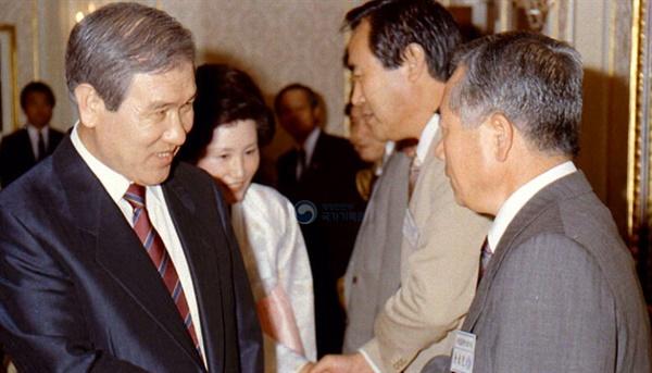 1989년 해외에서 개최된 국제영화제 수상자들을 격려하는 노태우 대통령이 김동호 당시 영화진흥공사 사장과 악수하고 있다.
