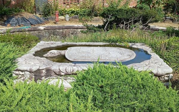 사랑채 앞 연못 상지에서 커다란 돌거북 한 마리가 물속에서 유영하며 안쪽을 바라보고 있다