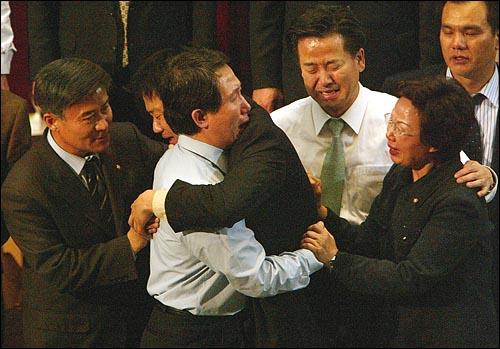 노무현 대통령 탄핵동의안이 한민공조속에 통과되자, 김근태 원내대표와 임종석 의원이 부둥켜안고 울고 있다. 옆에있던 정동영 의장과 김희선 의원도 눈물을 흘리고 있다.