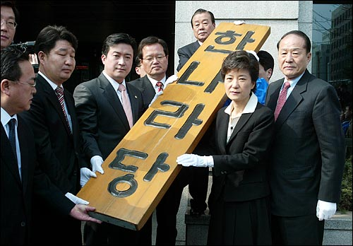 박근혜 한나라당 새대표와 당직자들이 새 당사로 이전하기 위해 구 당사에서 한나라당 현판을 떼어내고 있다.