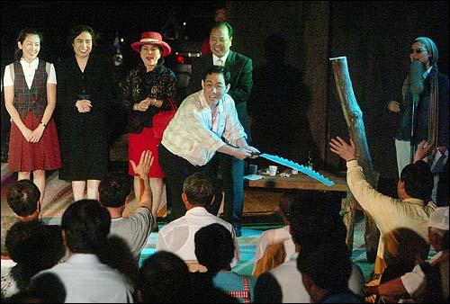 """한나라당 의원들로 구성된 `극단 여의도`는 28일 저녁 전남 곡성 봉조리 농촌체험마을에서 `환생경제`를 창단기념으로 공연했다. 공연을 마치고 아버지 `노가리`역을 맡은 주호영 의원이 무대인사를 하던도중 """"나라 절단낼까요""""하자, 의원들이 손을 내젖고 있다."""